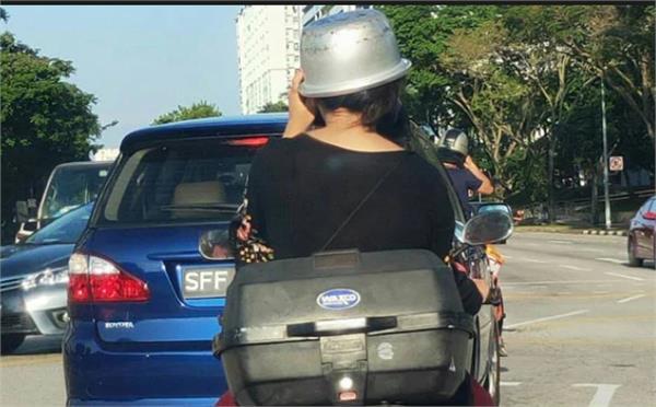 हेल्मेट नपाएपछि राइस कूकर टाउकोमा राखेर हिँडिन् यी महिला